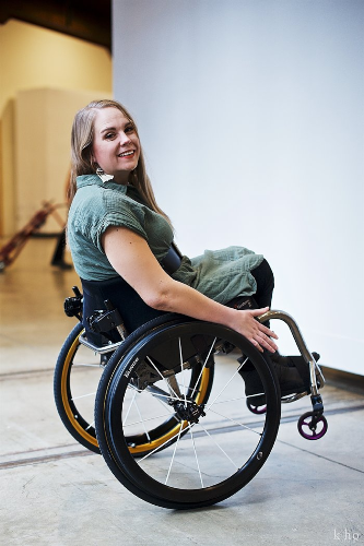 Harmanie posing in her wheelchair in a naturally lit room