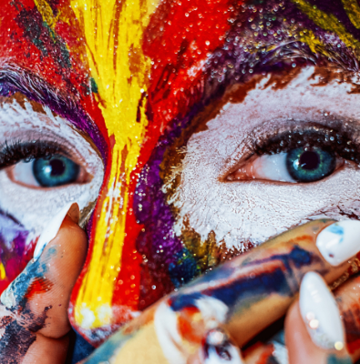 A close up of a face covered in paint. The person is covering their mouth with their hands that are also covered in paint. The person has blue eyes.