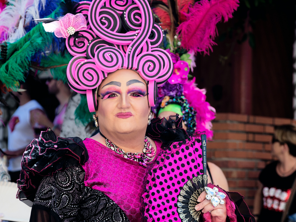 A drag queen dressed in vibrant colours of mostly pink with black polka dots. She is wearing pink eyeshadow and has a pink head piece on top of her head.