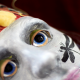 An image of a mask that has a grey face, with a black dragon fly painted on the left cheek. They eyes are blue with yellow and red decorative items placed on the forehead. The background of the whole image is a deep burgundy red.